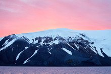 Red Sky Over Snowy Mountain And Water