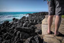 Man Walking On Path By Ocean And Black Lava Rocks