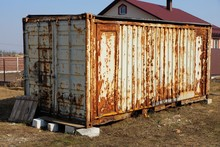 Large Old Gray Metal Container In Rust Stands On The Street