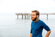 Germany, Rerik, bearded man in front of the sea looking at distance on hazy day