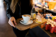 Close-up Of Woman Carrying Tray With Coffee And Soft Drink In A Self Service Cafe