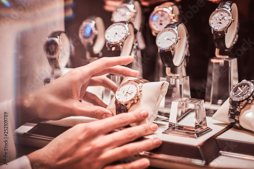 Obraz Close-up of the seller's hand shows the exclusive men's watch from the new collection in the luxury jewelry store - fototapety do salonu