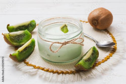 Photo sur Plexiglas Zen pierres a sable Yogurt with kiwi slices on a wooden white background.