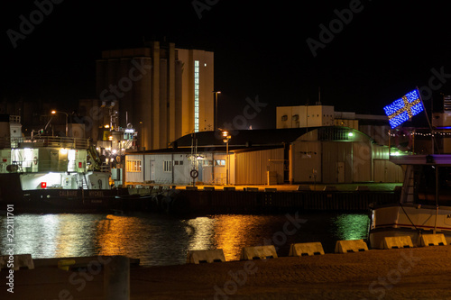Fotografía  Industrial harbor in the evening with a ship and silo