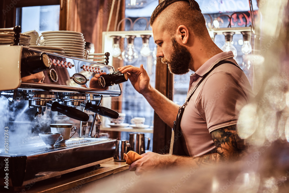 Fototapeta Handsome barista in uniform preparing a cup of coffee for a customer in the coffee shop