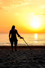 Man Silhouette With Metal Detector On The Beach