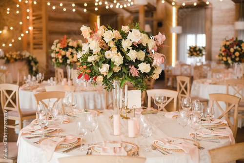 Obraz Coziness and style. Modern event design. Table setting at wedding reception. Floral compositions with beautiful flowers and greenery, candles, laying and plates on decorated table. - fototapety do salonu