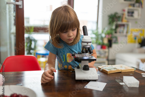 Fotografia  Little girl looking playing with microscope