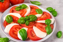 Caprese Salad With Ripe Tomatoes And Mozzarella Cheese, Fresh Basil Leaves On Concrete Background. Italian Food