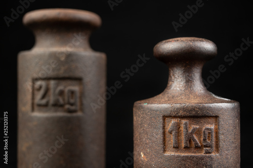 Fotografia  Old rusty metal weights for weighing products