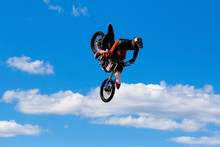JERSEY CITY, NJ - AUGUST 13, 2015: An Unknown Freestyle Motocross Rider Soars Through The Air Performing High-flying Stunts On A Motorcycle In Liberty State Park. The Extreme Sport Is Also Called FMX.
