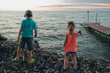 Rear View Of Siblings Looking At Sea While Standing On Pebbles Against Sky During Sunset