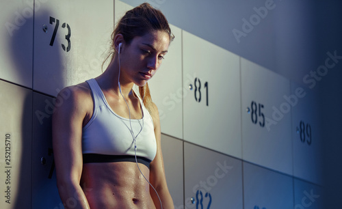 Fotografie, Obraz  Exhausted sweaty sportswoman listening music in gym's locker room
