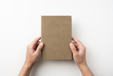 Man Hand Hold Brown Notebook On White Background