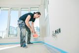 Fototapeta Łazienka - House under construction. Worker puts primer on concrete floor.