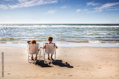 Netherlands, Zandvoort, boy and girl sitting on chairs on the beach