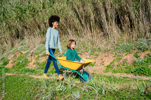 Father Walking On A Dirt Track Pushing Wheelbarrow With
