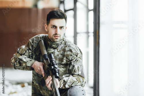 A young military soldier sits with a big rifle in his hands, near the window of Wallpaper Mural