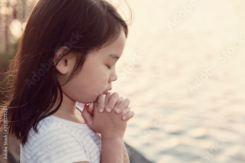 Fotografía Multicultural little girl praying with sunflare background