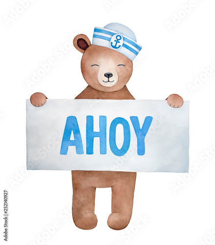 Photo Little smiling teddy bear character wearing white and blue striped sailor hat, holding paper sign with word Ahoy