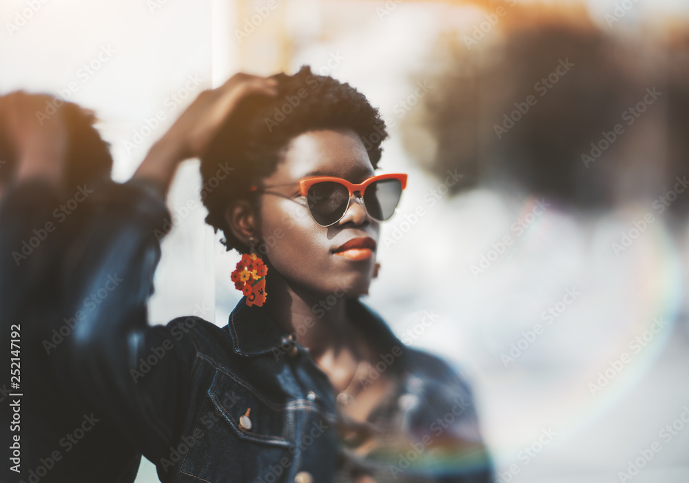 Fototapety, obrazy: True tilt-shift portrait of a young beautiful African female lit by the sun outdoors; charming fancy black female in sunglasses and with earrings leaning against a glass surface, selective focus