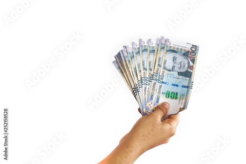 Fototapeta Close up of a hand holding 100 Peruvian soles bills in a fan shape on white background obraz