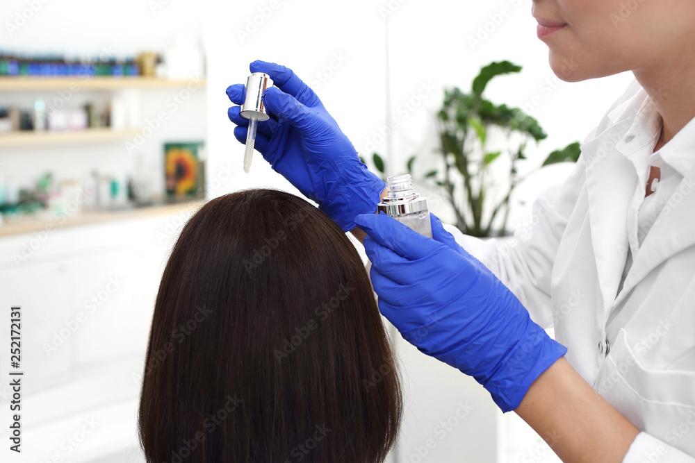 Fototapeta Zabieg przeciwłupieżowy. Pielęgnacja włosów. Dermatolog nakłada preparat leczniczy na skórę głowy kobiety.