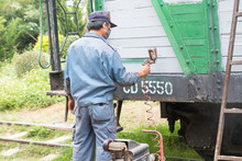 Painter Renovate Train Car By Color Spraying