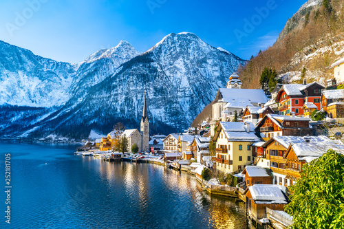 In de dag Alpen Classic postcard view of famous Hallstatt lakeside town in the Alps with traditional passenger ship on a beautiful cold sunny day with blue sky and clouds in winter, Salzkammergut region, Austria