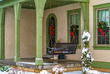 Home With Porch Swing And Welcoming Wreaths