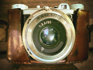 An old mechanical film camera, a background of wood