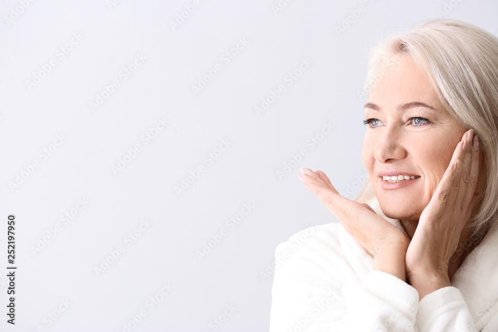 Fototapety, obrazy: Mature woman giving herself face massage on light background