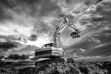 Crawler Excavator During Earthmoving Works On Construction Site In Black And White