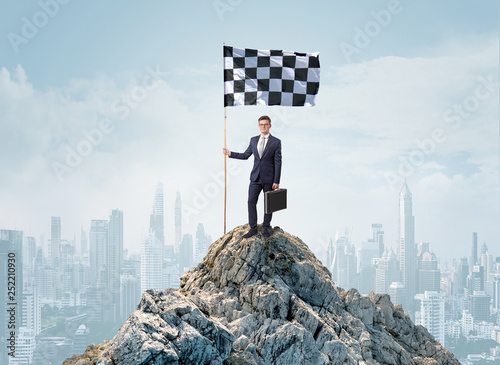 Successful businessman on the top of a city holding goal flag Canvas Print