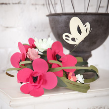 Closeup Of Paper Flowers On A Starov Desk With A Metal Cage And A Brick Wall In The Background.