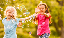 Two Toddler Girls Catching Soap Bubbles In Lavender Field