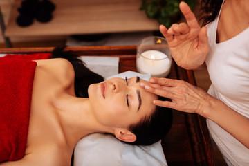 Obraz na płótnie Canvas Exotic expert woman in white uniform being unusual masseuse