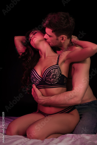 Spoed Foto op Canvas Hoogte schaal man passionately kissing beautiful young sexy woman in lingerie with neon red light isolated on black