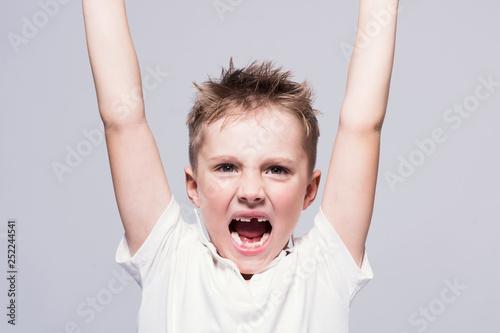 Fototapeta Angry toothless screaming little boy in a white T-shirt with arms raised up on a