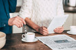 cropped view of man holding spoon near cup with coffee near wife holding digital tablet