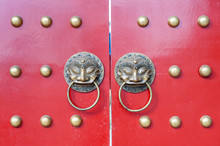 Golden Colored Chinese Door Knockers On A Red Gate