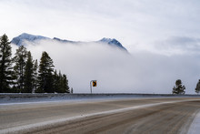 Encroaching Fog Along Canada Highway 93 Banff-Windermere Highway, In The Canadian Rockies Kootenay National Park During Winter. Icy Roads With Sand And Salt