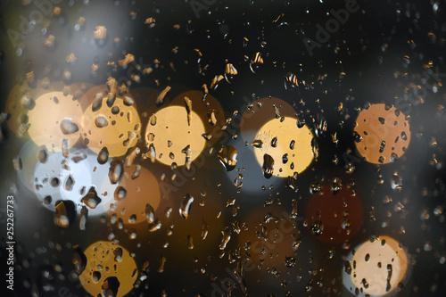 Krople deszczu na okiennej szybie, z kolorowymi światłami samochodów w tle. Miejski widok z okna, abstrakcja, deszczowa noc, bokeh - 252267733