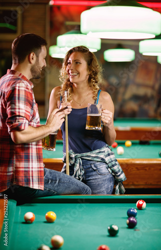 Fotografie, Obraz smiling woman flirting with man during billiard game.