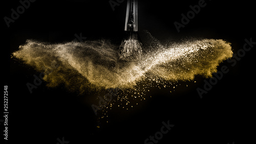 Türaufkleber Makrofotografie Cosmetic brush with golden cosmetic powder spreading for makeup artist and graphic design in black background, look like a luxury mood.