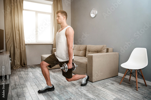 Photo Young well-built man go in for sports in apartment