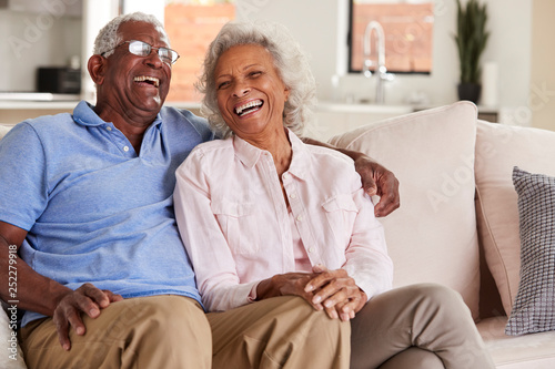 Photo Loving Senior Couple Sitting On Sofa At Home And Laughing Together