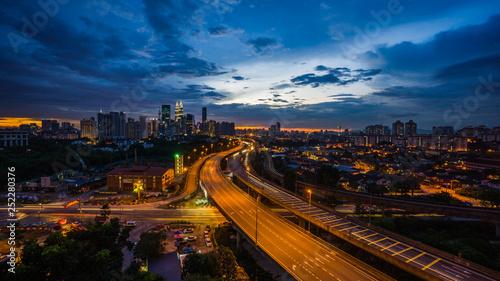 Foto op Aluminium Kuala Lumpur Kuala Lumpur city skyline during dramatic sunset with elevated highway leading into the city.