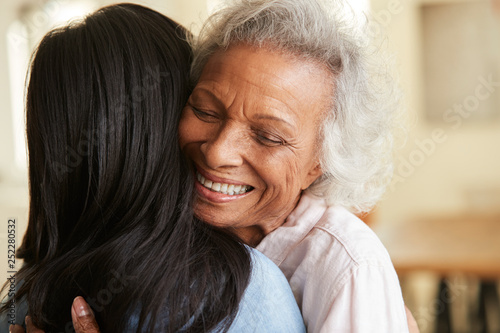 Fotografie, Tablou Over The Shoulder View Of Senior Mother Being Hugged By Adult Daughter At Home