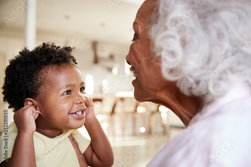 Grandmother Sitting On Sofa At Home With Baby Granddaughter Playing Game Togethe Canvas Print